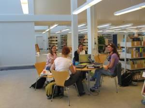 Studenter ved Aalborg universitet jobber i grupper i biblioteket